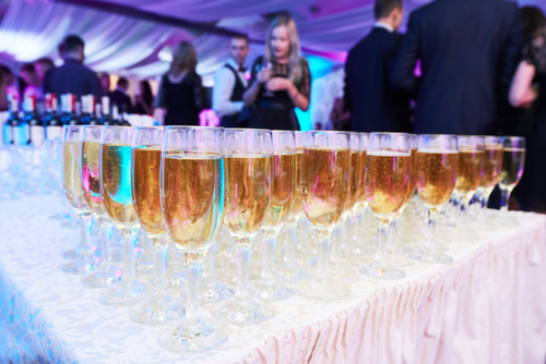 glasses with white sparkling wine in row at restaurant event